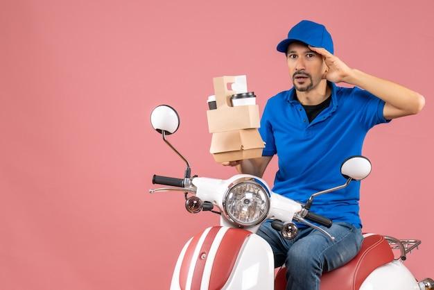 Vista dall'alto del corriere che indossa un cappello seduto su uno scooter che mostra gli ordini che si sentono confusi su uno sfondo di pesca pastello