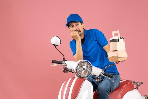 Vista dall'alto del corriere che indossa un cappello seduto su uno scooter che mostra gli ordini che si sentono spaventati su uno sfondo color pesca pastello