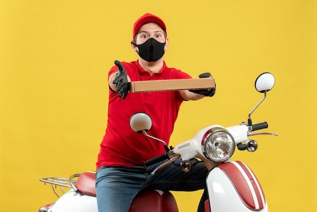 Vista dall'alto del corriere uomo che indossa camicia rossa e guanti cappello in mascherina medica che si siede sul motorino che dà ordine