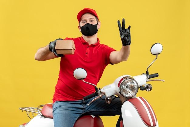 Vista dall'alto del corriere uomo che indossa camicia rossa e guanti cappello in mascherina medica seduto su uno scooter che tiene l'ordine che mostra tre