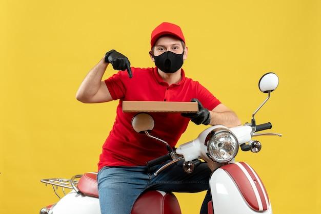 Vista dall'alto del corriere uomo che indossa camicia rossa e guanti cappello in mascherina medica che si siede sull'ordine di puntamento del motorino