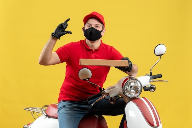 Vista dall'alto del corriere uomo che indossa camicetta rossa e guanti cappello in maschera medica seduto su uno scooter che mostra l'ordine che fa qualcosa di preciso