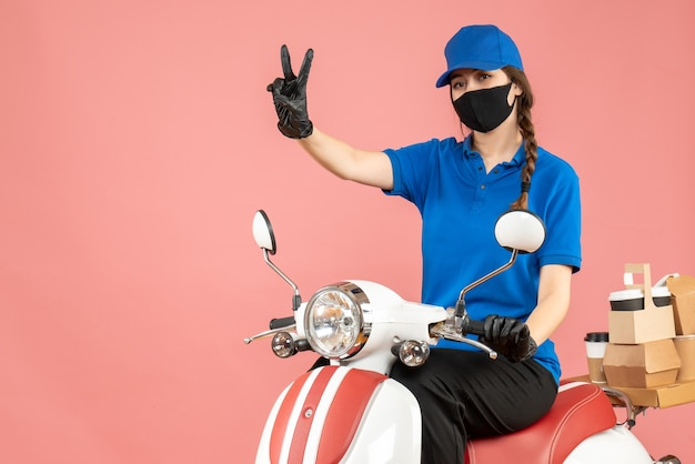 Top view of courier woman wearing medical mask and gloves sitting on scooter delivering orders making victory gesture on pastel peach background