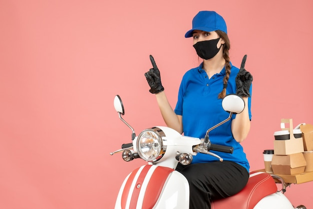 Top view of courier woman wearing medical mask and gloves sitting on scooter delivering orders pointing up on pastel peach background