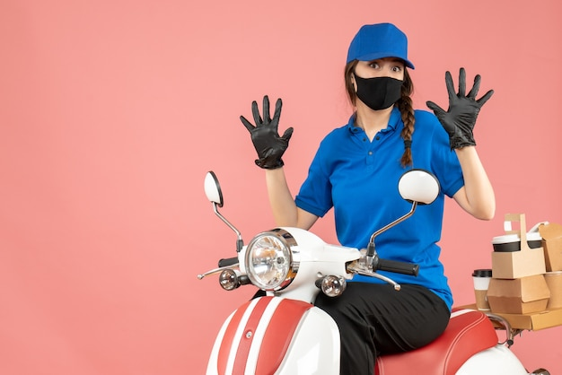 Top view of courier woman wearing medical mask and gloves sitting on scooter delivering orders showing ten on pastel peach background