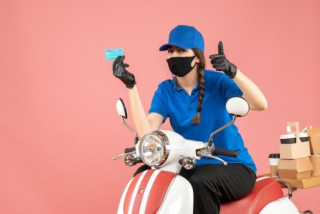 Vista dall'alto della donna del corriere che indossa maschera medica e guanti seduta su scooter con in mano una carta di credito che consegna ordini facendo un gesto ok su sfondo color pesca