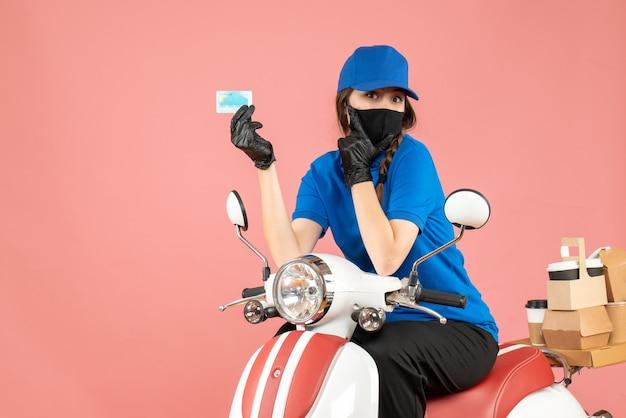 Vista dall'alto della donna del corriere che indossa maschera medica e guanti seduta su uno scooter con una carta di credito che consegna ordini su sfondo color pesca pastello