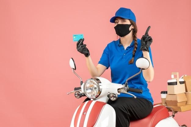 Vista dall'alto della donna del corriere che indossa maschera medica e guanti seduta su uno scooter con in mano una carta di credito che consegna ordini rivolti verso l'alto su sfondo color pesca pastello