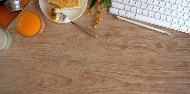 Top view of cozy workspace with a glass of orange juice and toast bread on wooden table