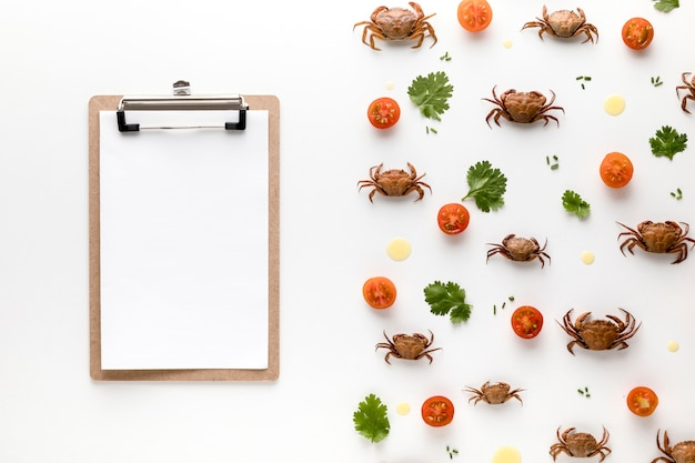 Top view of crabs and tomatoes with notepad