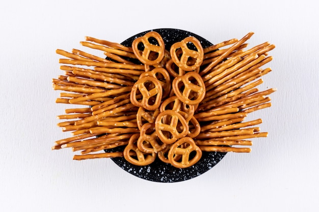 Top view crackers in black bowl on white  horizontal