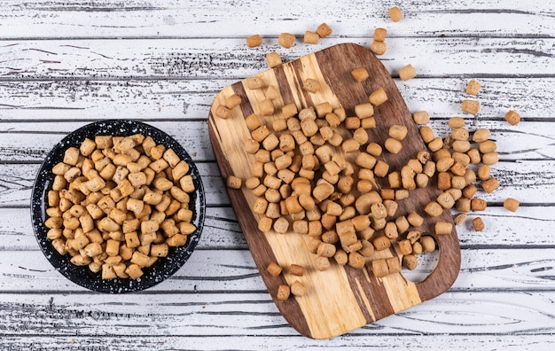 Top view of crackers in bowl and cutting board on white wooden  horizontal