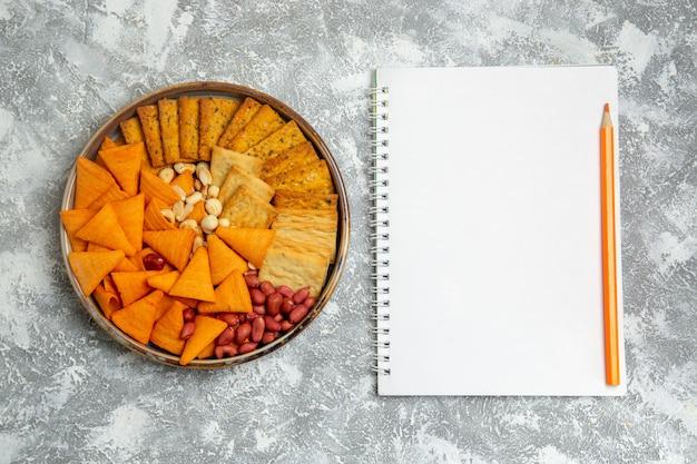 Vista dall'alto composizione cracker diversi cracker salati spuntini con noci su sfondo bianco croccante snack cracker