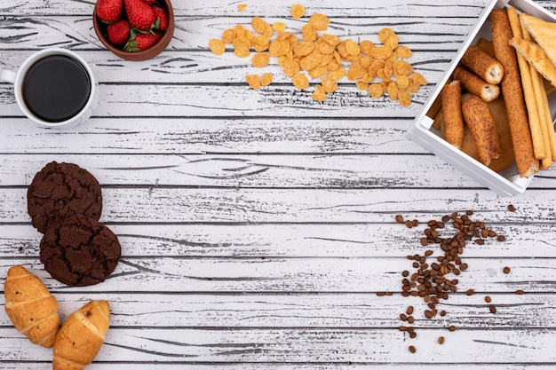 Top view of crackers and cornflakes with cookies, coffee and copy space on white wooden background horizontal
