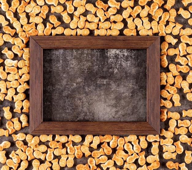 Struttura dei cracker di vista superiore con lo spazio della copia nel telaio di legno sull'orizzontale di pietra nero