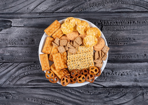 Top view crackers on white plate on gray stone  horizontal