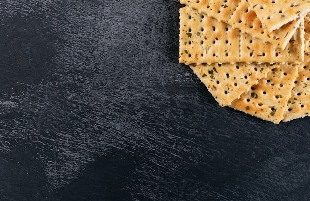 Top view crackers with copy space on black stone  horizontal