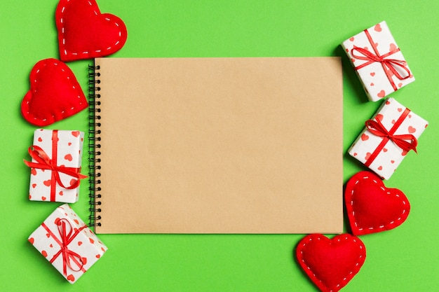 Top view of craft notebook surrounded with gift boxes and hearts