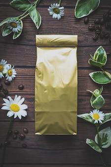 나무 테이블과 잎 주위에 꽃 위에 상위 뷰 공예 종이 파우치 가방