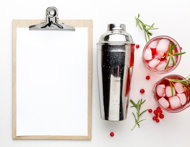 Top view cranberry vodka glasses with shaker and blank clipboard