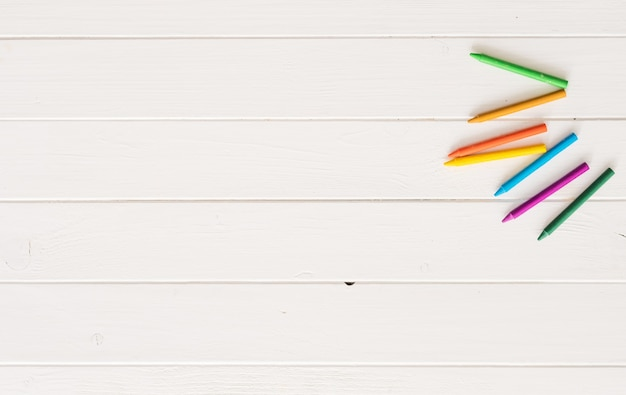 Top view of crayons on white wooden background
