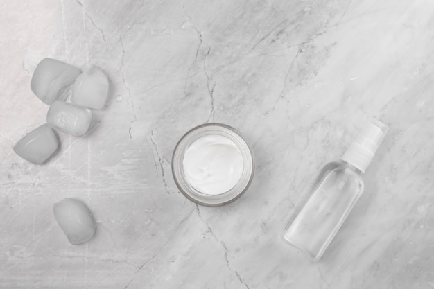 Top view of cream and bottle on marble background