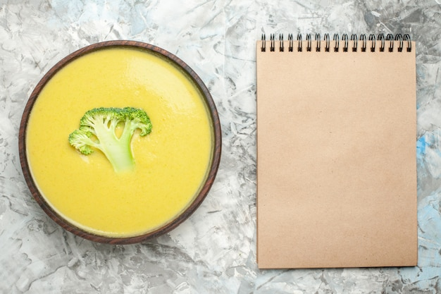 Top view of cream of broccoli soup in a brown bowl and notebook on white background