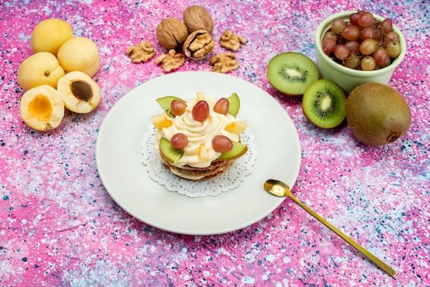 Вид сверху кремовый торт со свежими фруктами и грецкими орехами на цветном столе фруктовый торт бисквитного цвета
