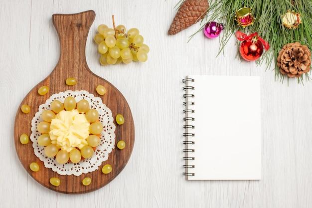 흰색 책상 과일 쿠키 케이크 비스킷 파이에 신선한 포도를 넣은 탑 뷰 크림 케이크