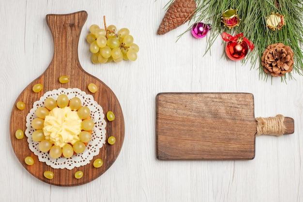 白い机の上の新鮮なブドウとトップビューのクリームケーキフルーツケーキビスケットパイクッキー