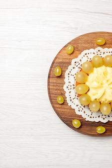 白い表面に新鮮なブドウのトップビュークリームケーキフルーツケーキビスケットパイクッキー