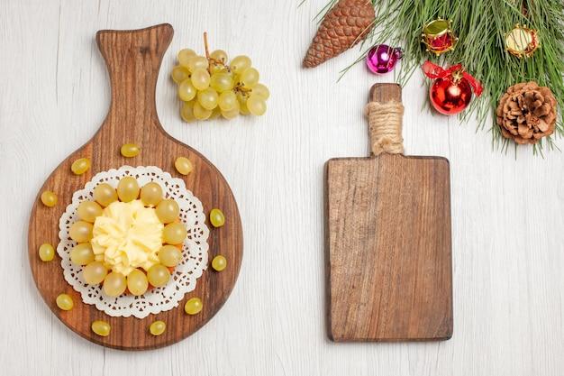 Torta alla crema vista dall'alto con uva fresca su scrivania bianca torta alla frutta biscotto torta biscotto