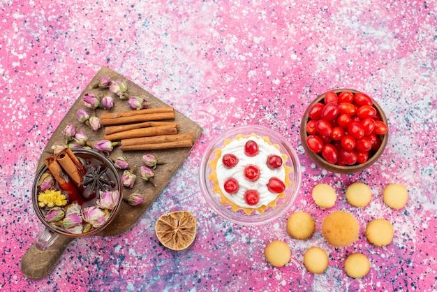 Вид сверху кремовый торт со свежей красной клюквой, печеньем с корицей и чаем на ярком столе, сладкое