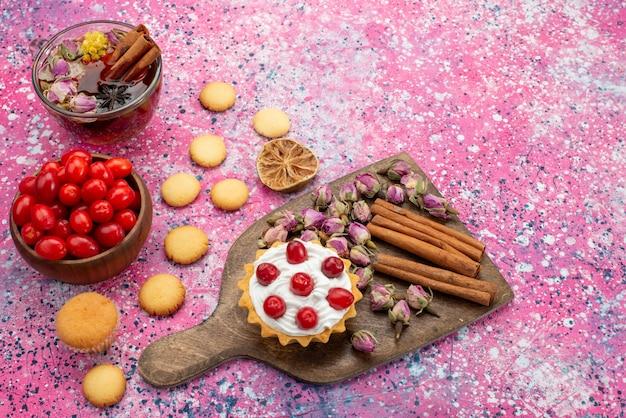 Вид сверху кремовый торт со свежей красной клюквой, печеньем с корицей и чаем на ярком настольном сахаре