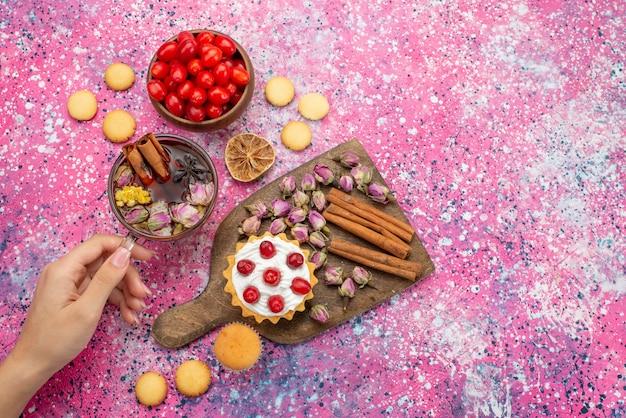 Вид сверху кремовый торт со свежей красной клюквой, печеньем с корицей и чаем на фиолетовом столе, сладкое