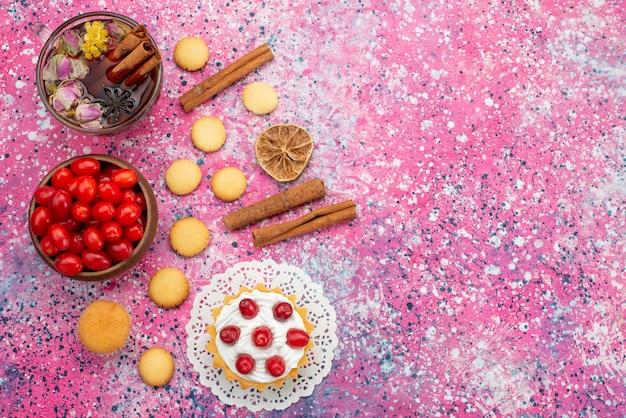 Вид сверху кремовый торт со свежей красной клюквой вместе с печеньем с корицей и чаем на фиолетовой поверхности сладкого сахара