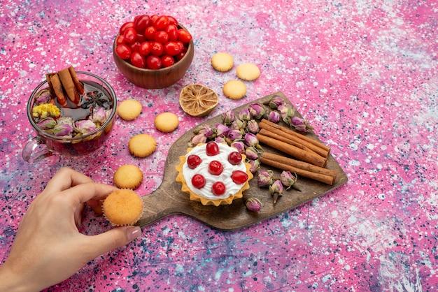 Вид сверху кремовый торт со свежей красной клюквой вместе с печеньем с корицей и чаем на сияющем столовом сахаре