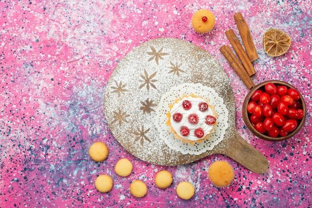 Вид сверху кремовый торт со свежей красной клюквой вместе с печеньем с корицей на светлом бисквитном полу с ягодами сладких фруктов