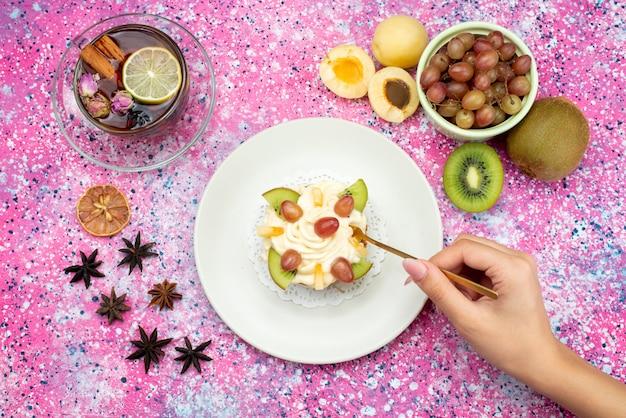 トップビューのクリームケーキ、キウイアプリコット、色付きの背景にお茶ケーキ砂糖甘い生地焼きフルーツ