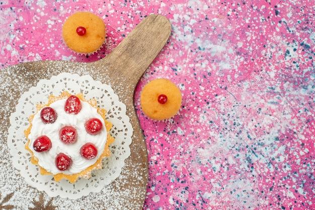 Вид сверху кремовый торт с красными фруктами на ярком столе сахарный сладкий чай