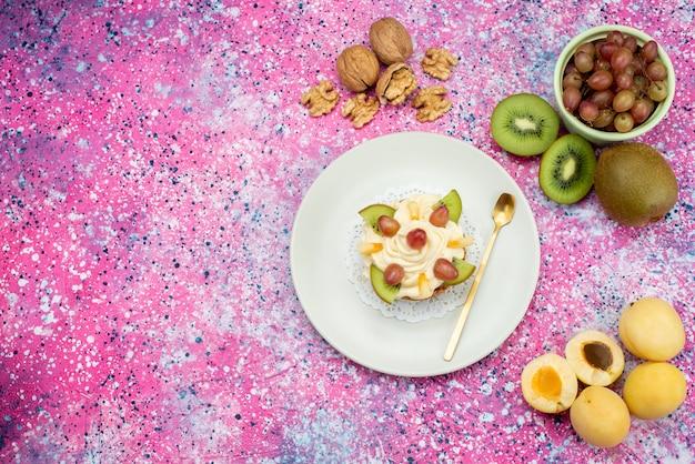 Вид сверху кремовый торт с грецкими орехами свежие фрукты на фиолетовом фоне цвет торт бисквит сладкий
