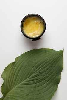 Top view of cream and leaf on white background