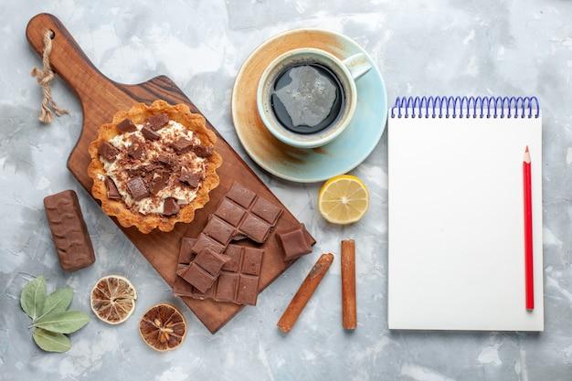 トップビュークリームの小さなケーキとチョコレートバーと軽い机の上のお茶甘いケーキシュガーチョコレート