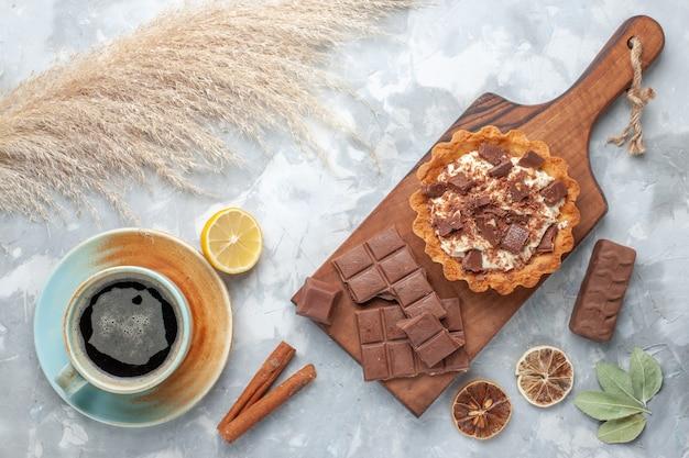 Top view crema piccola torta con barrette di cioccolato e tè sulla scrivania leggera torta dolce crema di zucchero al cioccolato