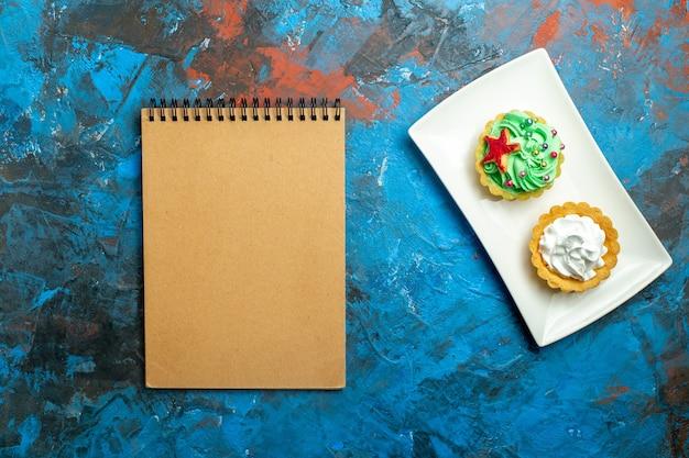 青赤の表面のプレートノートブックの上面クリームタルト