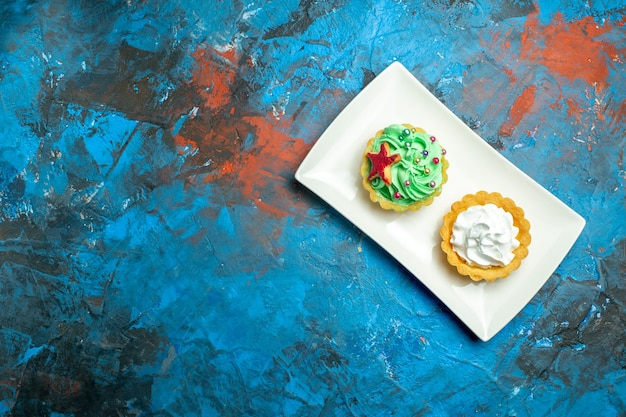 Top view cream tarts on white rectangular plate on blue red surface free space