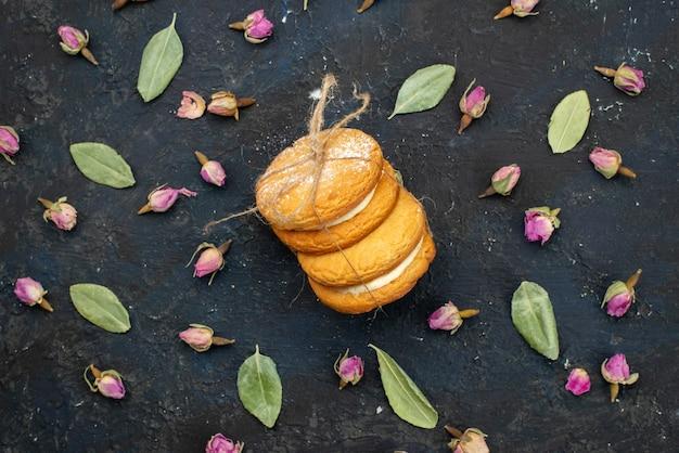 Вид сверху сливочное печенье-сэндвич d вкусно изолированное на темной поверхности торт сахарное сладкое печенье