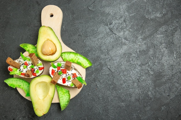 Top view of creamy avocados with bread and pepper and fresh avocados on a grey surface