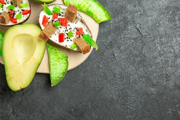 Top view of creamy avocados with bread and pepper and fresh avocados on the grey surface