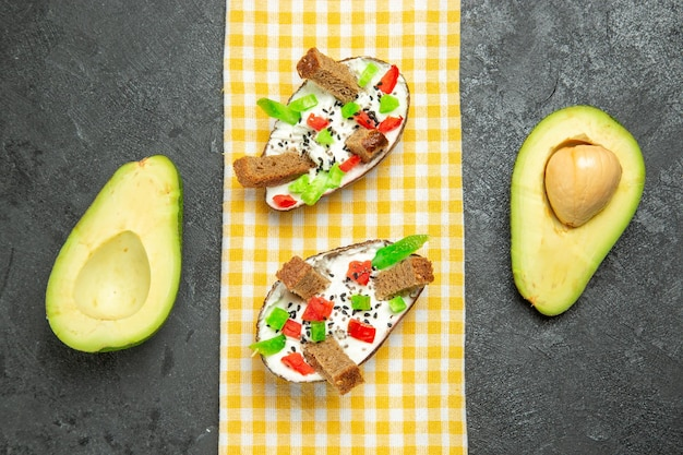 Top view of creamy avocados with bread and pepper on grey surface